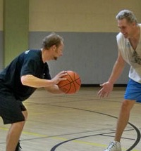 Adults playing basketball in school gym.