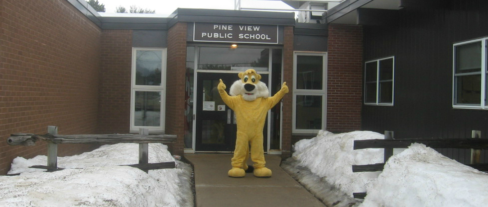Victor the Lion Mascot in front of the school