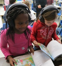 Students listening to the story while following with the book.